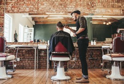 Rear view shot of handsome hairdresser cutting hair of male client. Hairstylist serving client at barber shop.