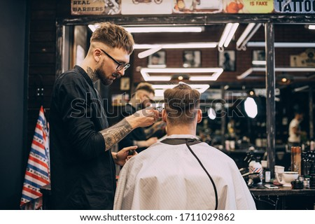 Rear view shot of handsome hairdresser cutting hair of male client. Hairstylist serving client at barber shop. Hipster young good looking man visiting hairstylist in barber shop. Stock fotó ©