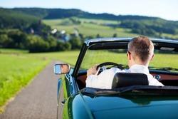 Rear view shot of man driving a convertible car outdoors