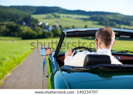 Rear view shot of man driving a convertible car outdoors #140234707