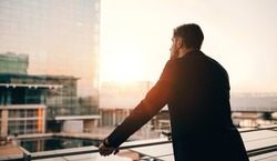 Rear view shot of young businessman standing in airport lounge balcony and looking outside. Man waiting for his flight in airport terminal.