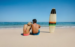Rear view shot of young man and woman sitting on the beach with surf board. Couple relaxing on the sea shore on a summer day.