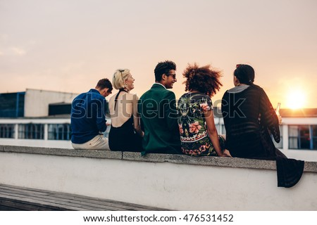 Rear view shot of young men and women sitting together on rooftop. Mixed race friends relaxing on terrace during sunset.