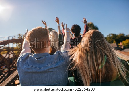 Rear view shot of young people on a thrilling roller coaster ride at amusement park. Group of friends having fun at fair and enjoying on a ride.