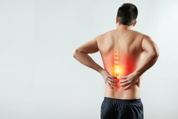 Rear view, the man holds his hands behind his back, pain in the back, pain in the spine, highlighted in red. Light background. The concept of medicine, massage, physiotherapy, health.