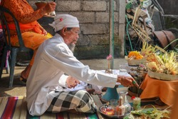Rear view to Hindu priest praying during a wedding ceremony. Pedanda sits on the ground in front of the offerings and performs wedding ceremonies.
