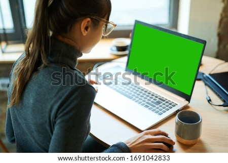 Rear view woman freelancer in eyeglasses working in cafe, using laptop computer with a green screen on monitor. Concept remote work, freelance, working on laptop computer or net-book.