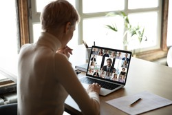 Rear view woman sit at desk learns new videoconference app online review, look at pc screen take part in group video call with corporate staff brainstorm distantly, study, work use modern tech concept