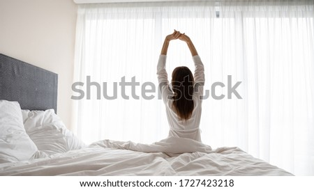 Rear view woman wake up sit in bed raised hands stretching body start day right with exercises, increases muscles tone encouraging joints flexibility, energy boost, enjoy new day, good morning concept