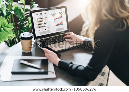 Rear view. Young businesswoman is sitting at table, working on laptop with graphs, charts, diagrams, schedules on screen. Online marketing, education, analytics, e-commerce, business planning #1050596276