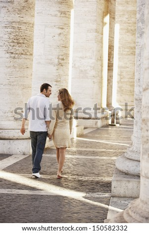 Rear view young couple walking between pillars in Rome; Italy