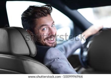 rear view, young man driving his car, looking at camera