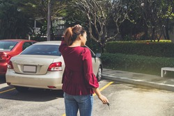Rear view young woman stood with keys looking for her car in the parking lot, but couldn't find it : Woman was dazed because her car had been lost through the stolen