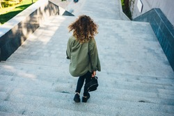 Rear view young woman with curly hair coming down stairs in city on summer day.
