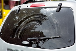Rear window of a dirty car with a faulty wiper, close-up of a dirty poorly wipe window.