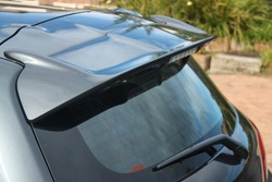 Rear windscreen and roof spoiler of a grey hatchback