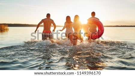 Rearview of a group of diverse young friends in swimsuits splashing water while running into a lake together on a late summer afternoon #1149396170