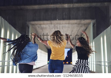 Rearview of a group of diverse young girlfriends holding hands while walking together in the city at night