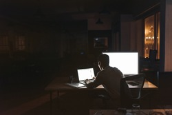 Rearview of a young businessman sitting alone at a desk in a dark office working on a laptop late in the evening