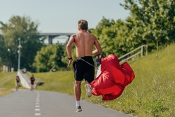 Rearview of an attractive shirtless young man running with a resistance parachute in the park