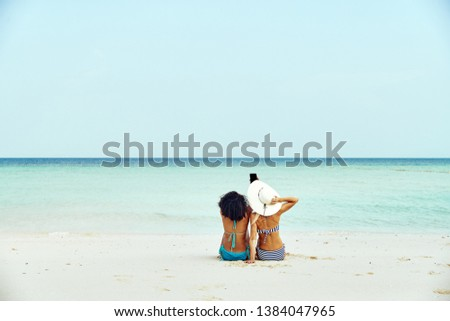 Rearview of two young female friends wearing bikinis and taking selfies while suntanning on a sandy beach during a tropical vacation