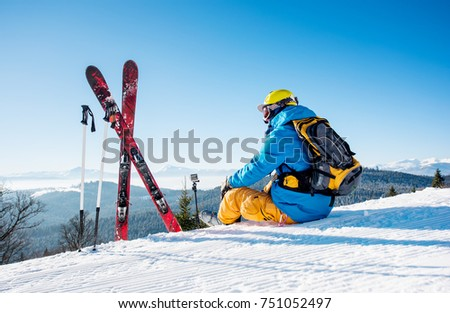 Rearview shot of a skier sitting on top of the mountain near his skiing equipment relaxing enjoying beautiful snowy mountains view people living enjoyment recreation travelling riding #751052497