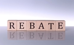 REBATE concept, wooden word block on grey background