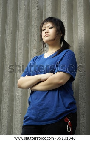 stock photo : Rebellious asian teen girl leaning against wall