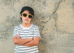 rebellious boy with sunglasses next to a wall outdoors