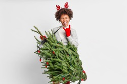 Rebellious dark skinned woman sticks out tongue and makes horns gesture being crazy rocker holds christmas tree like guitar wears reindeer antlers has fun one New Year party. Winter time concept