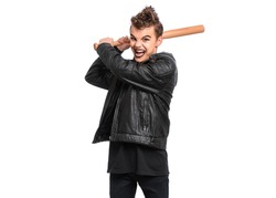Rebellious teen boy dressed in black, isolated on white background. Young teenager in style of punk goth wearing leather jacket, holding wooden bat. Problems of transitional age