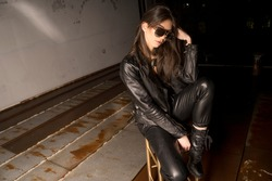 Rebellious young woman in black leather clothing with sunglasses sitting in a chair in an abandoned room