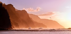 Receding headlands of the Na Pali Kauai coastline illuminated at sunset over a stormy sea with a distant bird. The mountains off Ke'e beach are the start of the Kalalau Trail