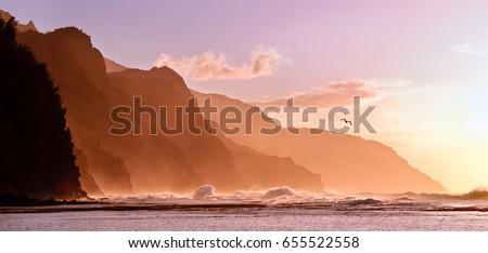 Receding headlands of the Na Pali Kauai coastline illuminated at sunset over a stormy sea with a distant bird. The mountains off Ke'e beach are the start of the Kalalau Trail #655522558
