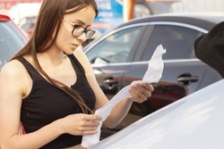 receipt from a supermarket,woman looks at a check in the parking lot of a store