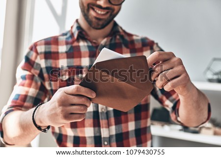 Receiving greeting card. Close up of young man opening envelope and smiling while standing indoors #1079430755