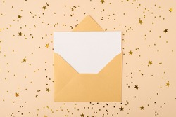Receiving invitation concept. Top close up flat lay layout view photo of open unpacked unwrapped gold envelope and clear card inside for mock up on shiny confetti background