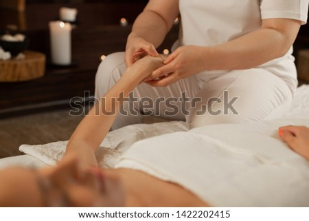 Receiving relaxing massage . Experienced massage master pressing on dots on the hand of her client during pleasant procedure #1422202415