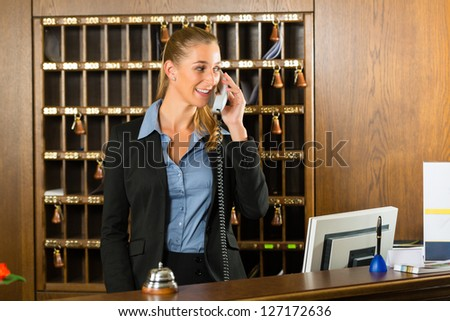 Reception of hotel, desk clerk, woman taking a call and smiling
