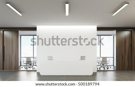 Reception table with two laptops and conference room with glass walls in the background. Concept of company office. 3d rendering. Mock up.