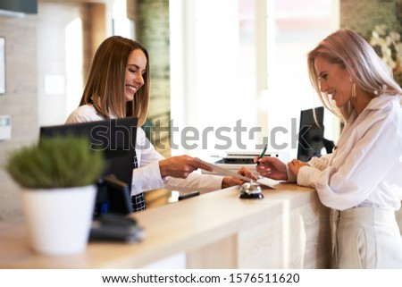 Receptionist and businesswoman at hotel front desk Photo stock ©