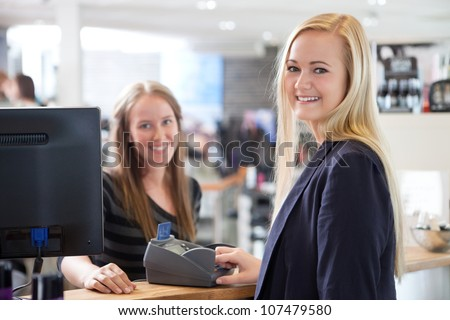 Receptionist and client in beauty salon paying with credit card.