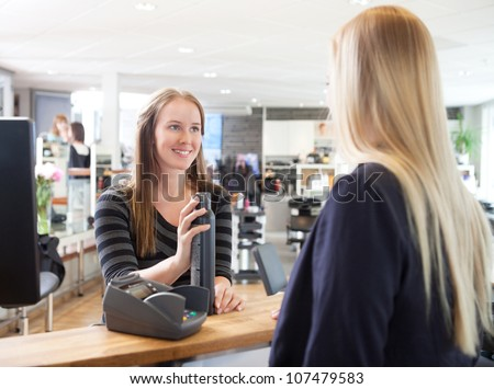 Receptionist and client in beauty salon swiping credit card.