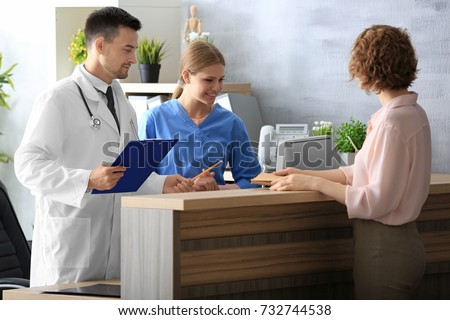 Receptionist and doctor with client in hospital