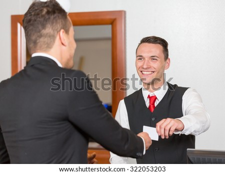 receptionist at hotel reception handing key card to guest or client