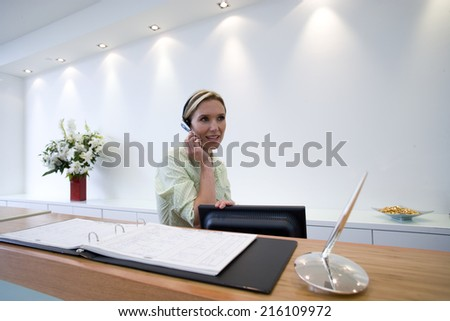 Receptionist behind desk with headset