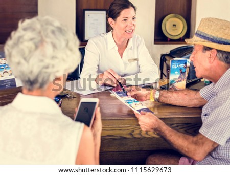 Receptionist giving explanations to a senior man