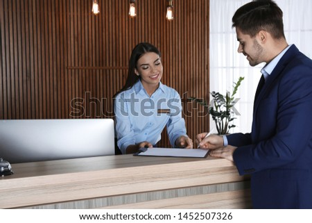 Receptionist registering client at desk in lobby Stock photo ©