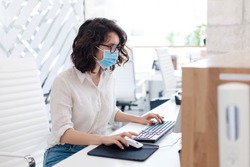 Receptionist wearing medical mask in office. Protection employees on workplace. Young woman working at reception in hotel. Social distancing during quarantine, staff safety.