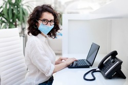 Receptionist wearing medical mask in office. Protection employees on workplace. Young woman working at reception in hotel. Social distancing during coronavirus quarantine, staff safety from covid 19.
